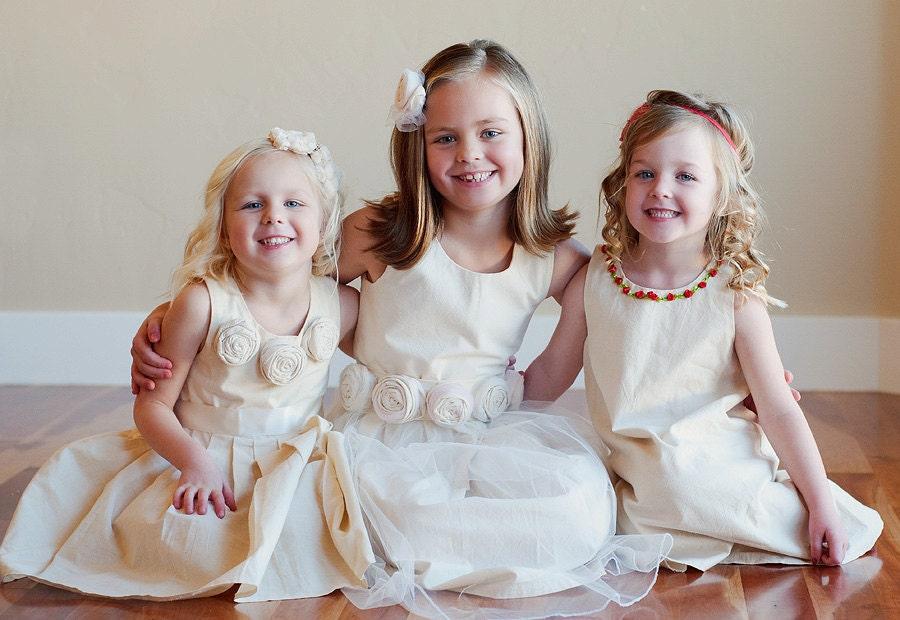 دختر گل یا لباس ساقدوش عروس در پنبه است. لباس تغییر ساده با جزئیات گل. با یا بدون کمربند