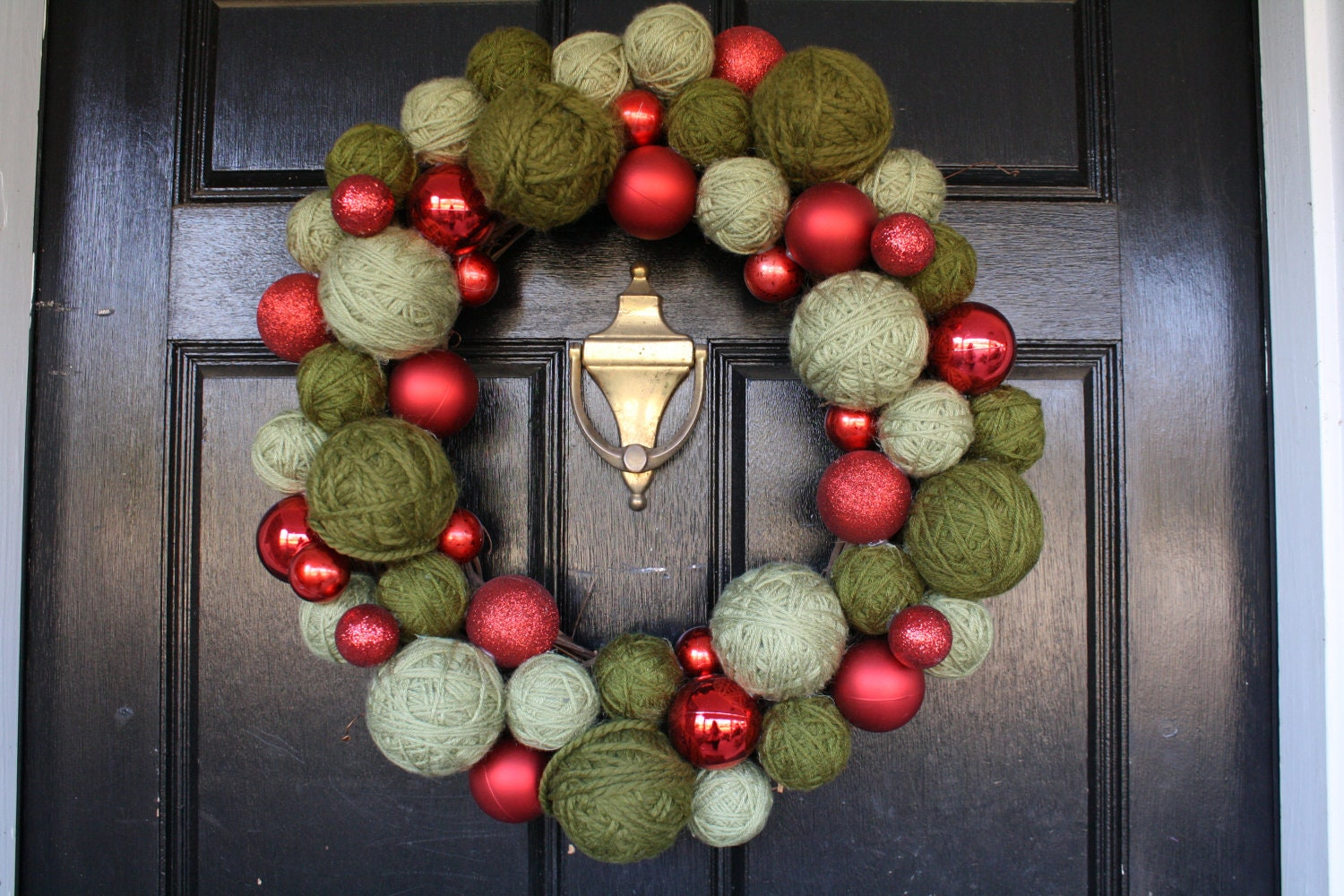 Christmas Wreath Red Christmas balls and green yarn balls on a grapevine wreath