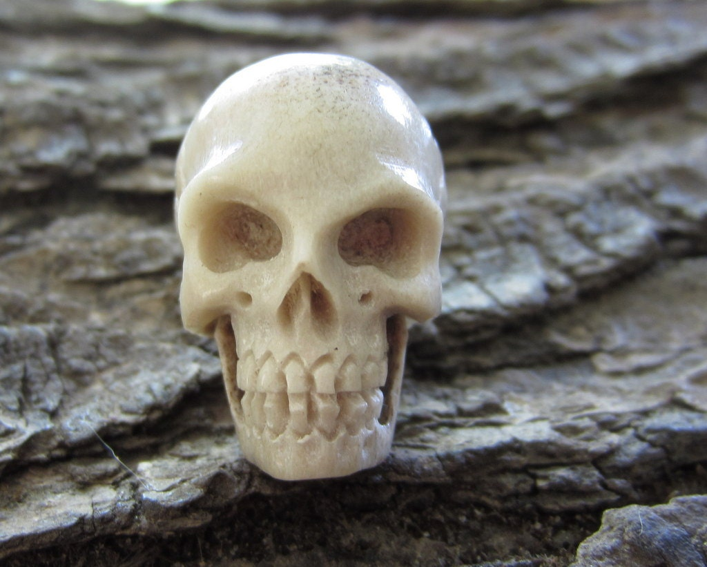 Deep relief carving human skull from deer antler bone by
