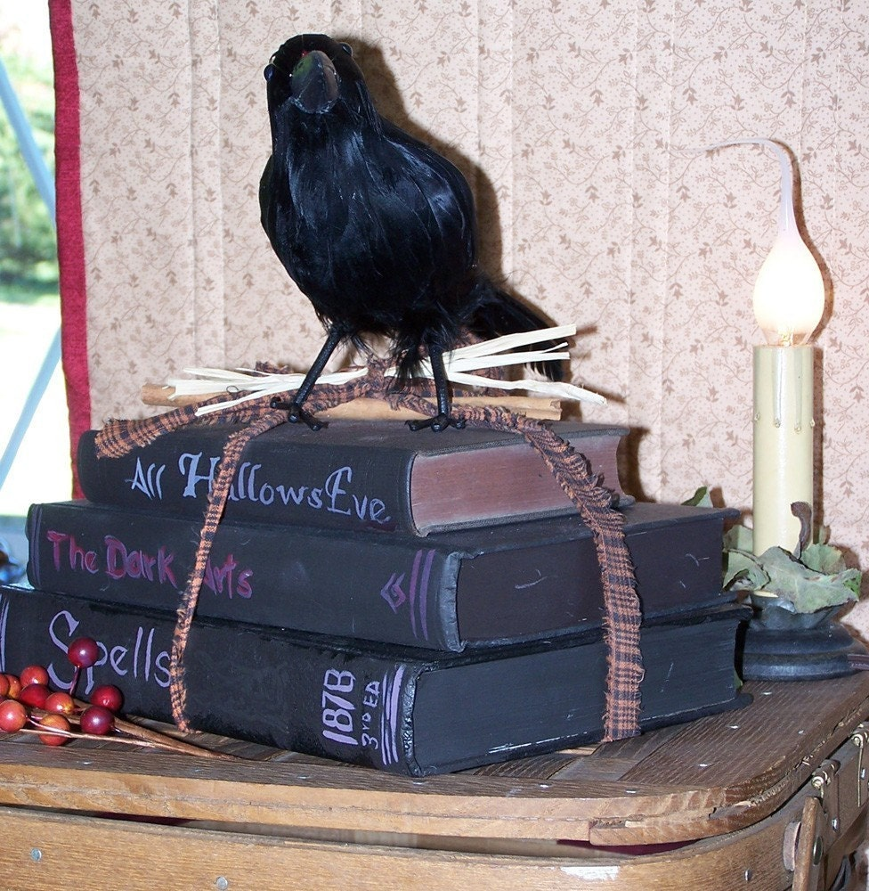 a crow sitting on top of a  stack of altered books books  spells the dark arts all hallows eve