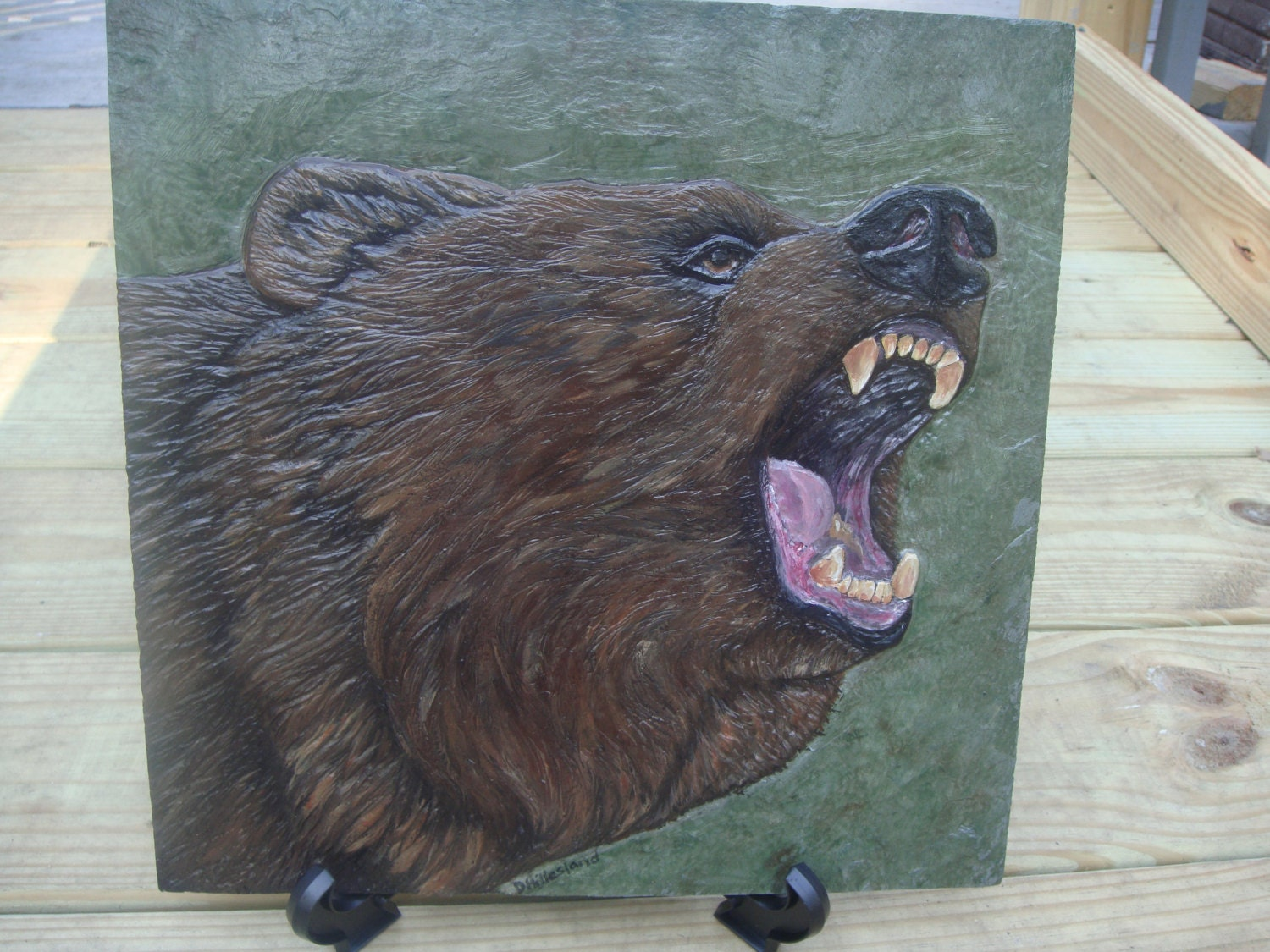 Relief carved grizzly bear on slate stone tile by