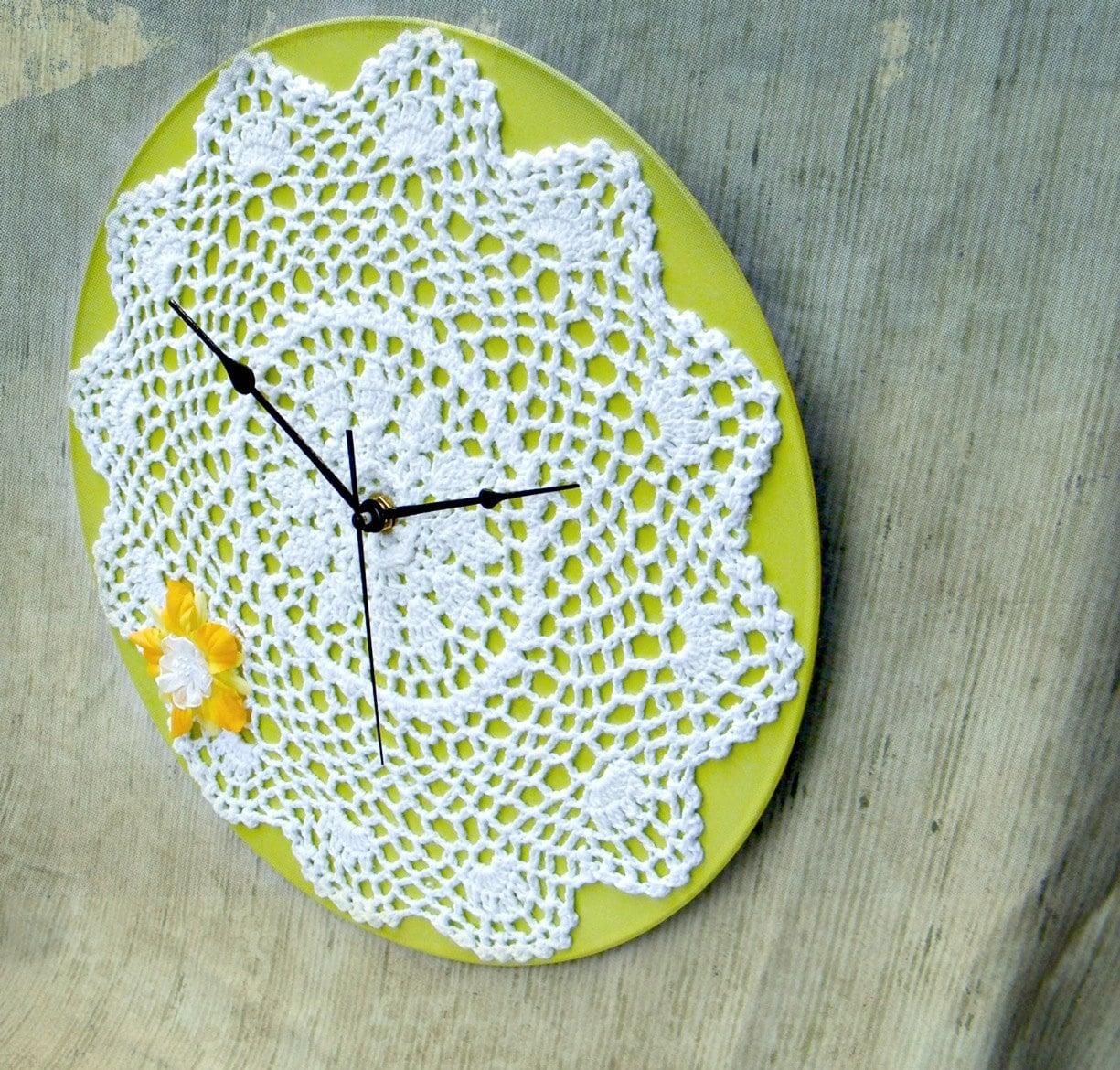 Круглые настенные часы, украшенные вязаной салфеткой и цветком