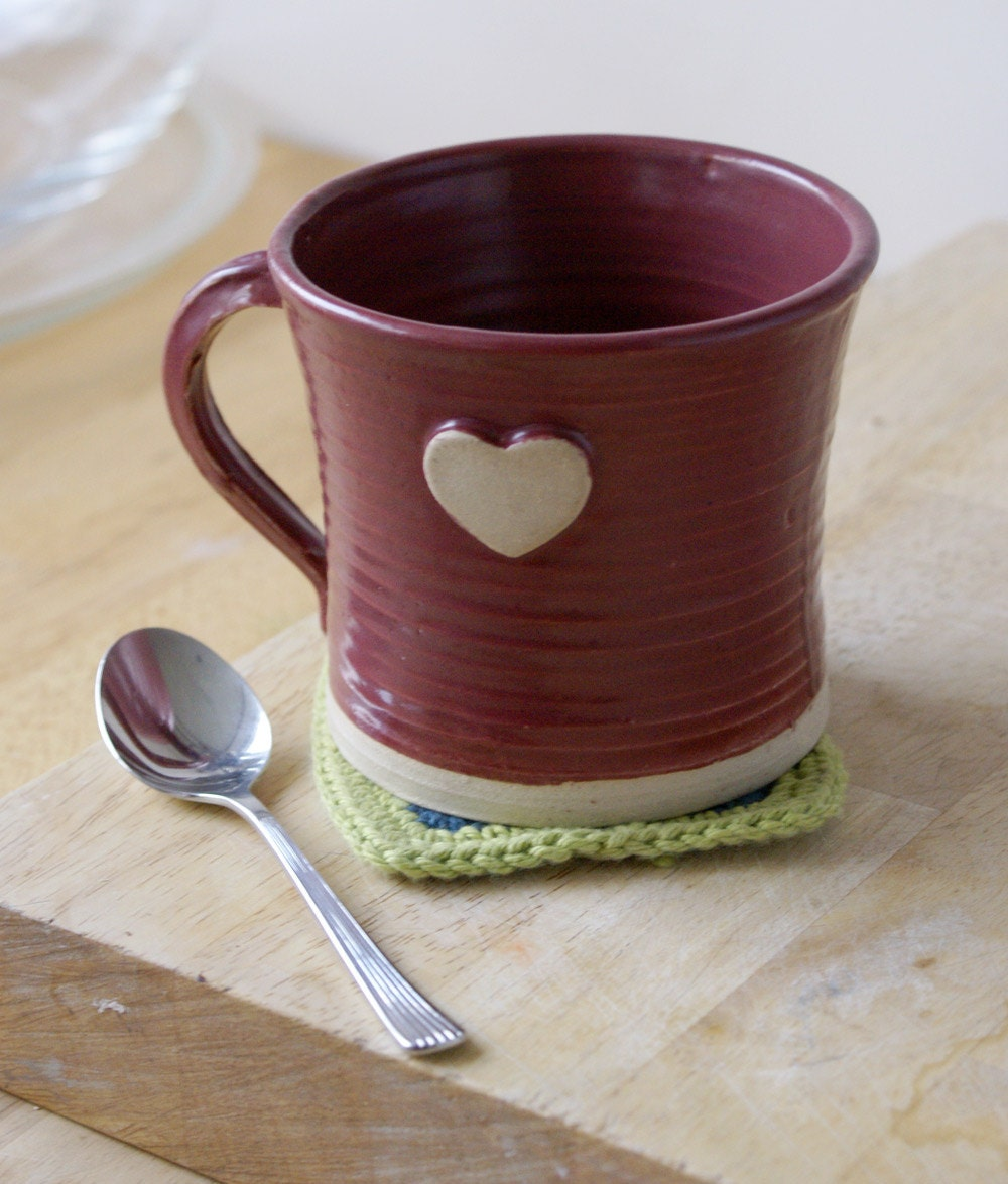 Picture of a red pottery mug with small white-brown heart on it