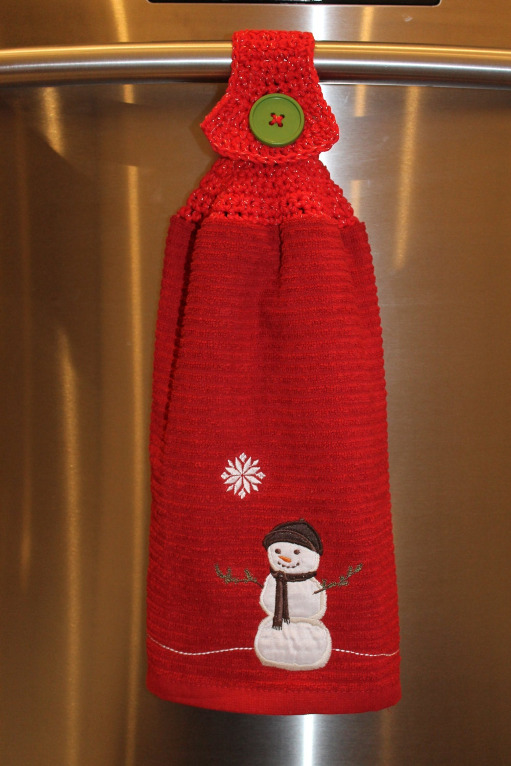 Snowman dish towel with crochet topper on by chainstitchers