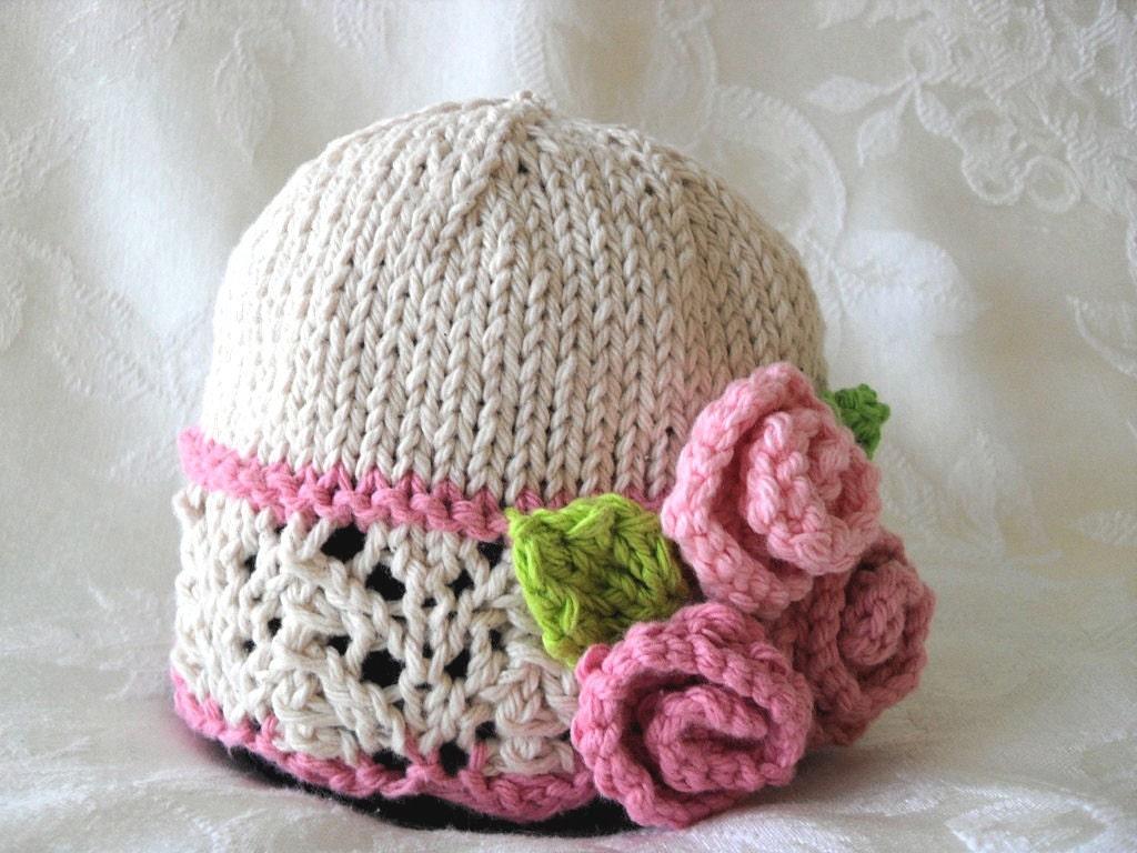 کودک کلاه بافتنی -- کلاه دست کودک را در توری صورتی و عاج با گل سرخ ، غرور و شادی بافتنی
