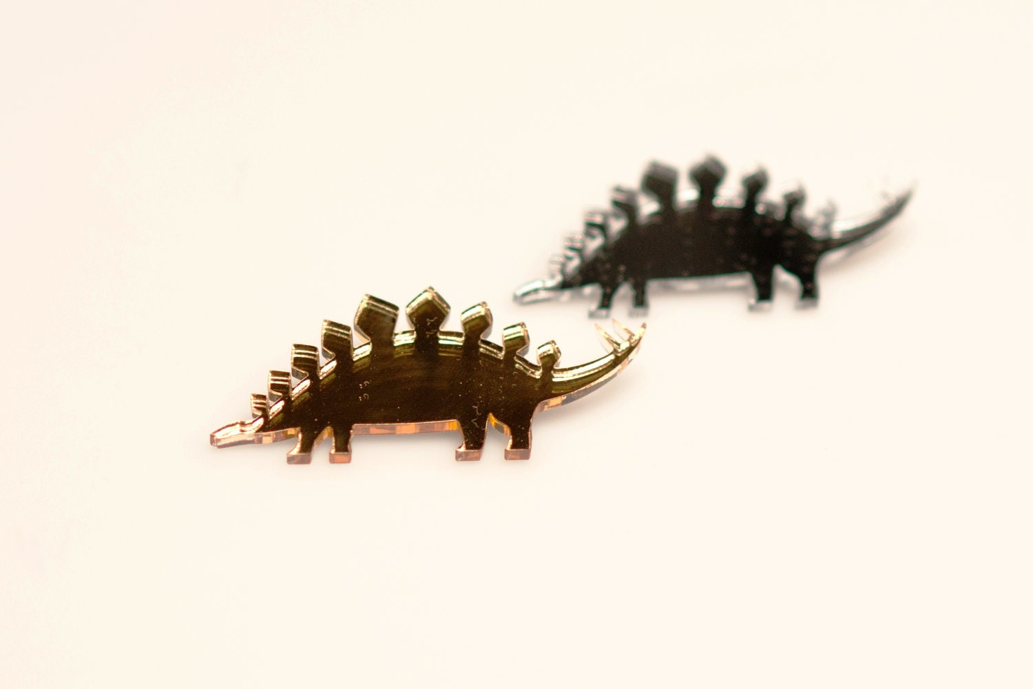 Two stegosaurus lasercut brooches