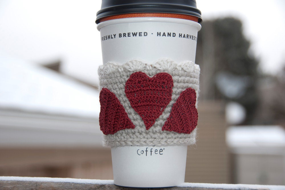 Hand crocheted coffee cosy cozy, three red be mine valentine gift hearts on a linen sleeve with a snow white lace trim