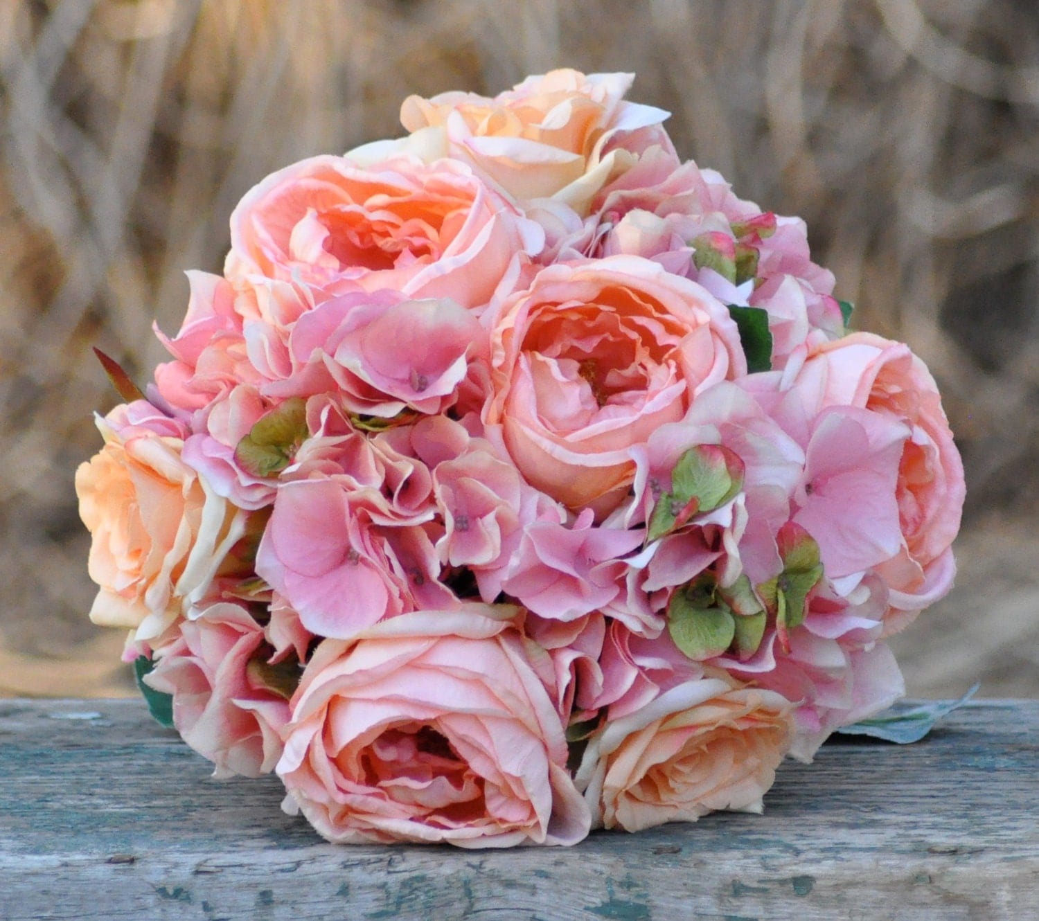 Coral rose and pink hydrangea wedding bouquet made of silk roses.