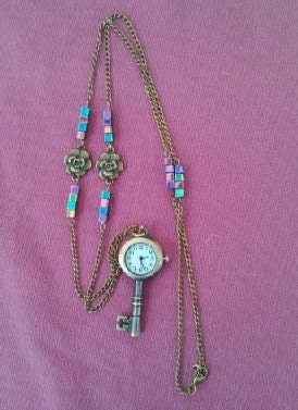 Necklace style key shaped pocket watch with rainbow hematite and flower chain