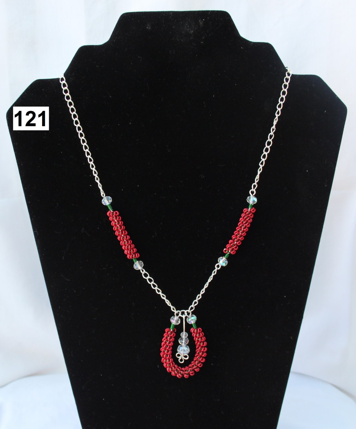 A Red and Green Horseshoe Shaped Coiled Necklace using Jewellery Wire and Clear Faceted Beads Silver Coated Wire Trefoil Wirework