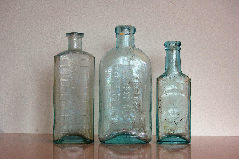 Glass bottles vintage set of three antique light blue by for Uses for old glass bottles